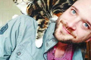 парень в голубой рубашке котом на плече